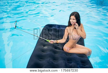 Pretty Female In Bikini Smiling And Taking Selfie Photo On The Phone With Selfie Stick On A Mattress
