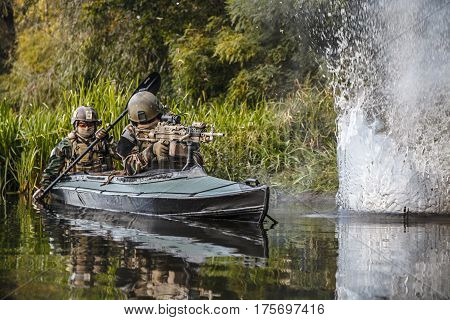 Special forces men with painted faces in camouflage uniforms paddling army kayak. Sudden nearby bomb explosion, water blast