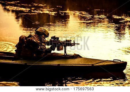 Special forces backlit machine gunner in army kayak. Boat moving calmly across the river, diversionary mission, sunset dusk