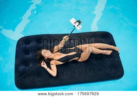 Smiling Girl In Black Bikini Lying On An Inflatable Mattress In Swimming Pool And Makes Selfie Photo