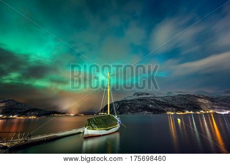 Northern lights in the Norwegian fjord and the yacht. The landscape of the Northern nature. Winter. Mountains covered with snow