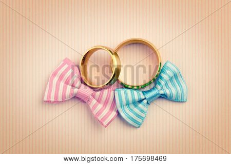 Vintage style Wedding card background - two gold wedding rings and two bowknots, retro toned