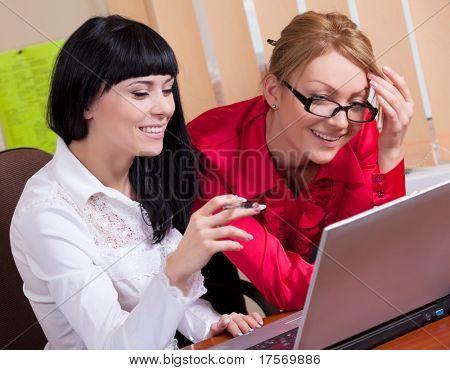 Mujeres muy jóvenes en lugar de mirar la pantalla del ordenador
