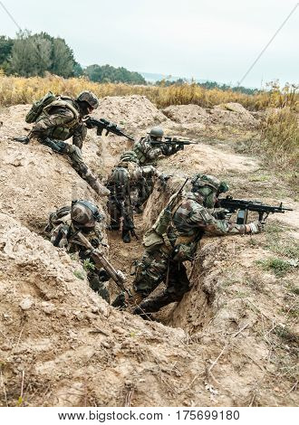 Squad of elite french paratroopers of 1st Marine Infantry Parachute Regiment RPIMA taking control enemy trenches, securing positions