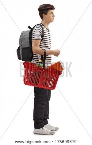 Full length profile shot of a teenage student waiting in line with a shopping basket isolated on white background