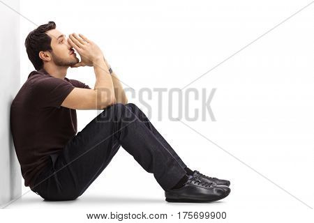 Pensive man leaning against a wall and thinking isolated on white background