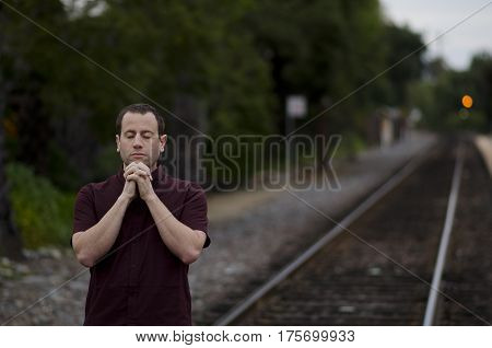Man praying alone by train tracks with hands clasped together.