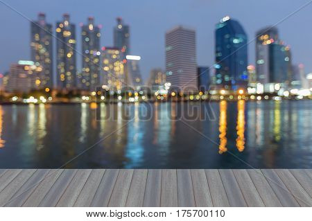 Opeing wooden floor twilight night view city building with reflection abstract background