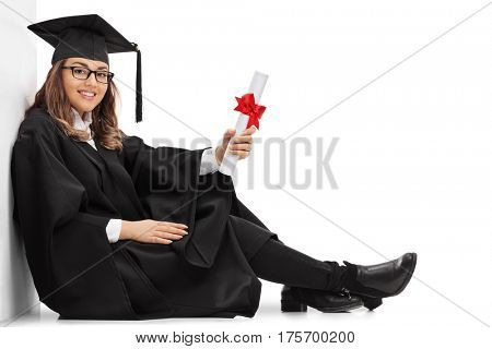 Happy graduate student with a diploma sitting on the floor and leaning against a wall isolated on white background