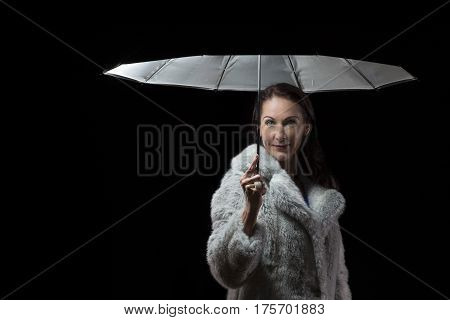 Beautiful woman with white fur coat standing in rain under an umbrella at night