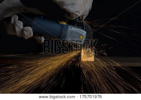 Angle grinder cutting a metal square tube making a shower of sparks