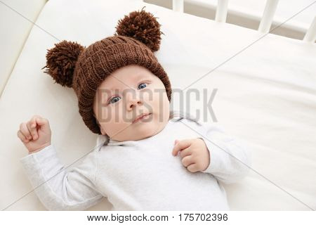 Cute little baby lying in cradle at home