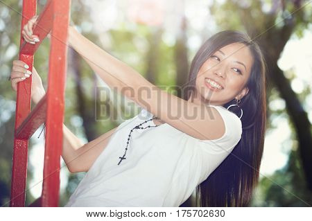 Smiling Asian lady taking fun at red staircase