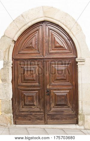 Massive oak decorative door on marble facade