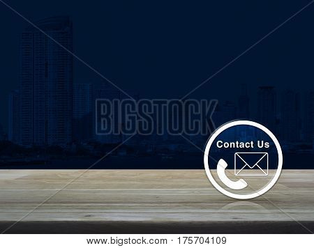 Telephone and mail icon button on wooden table over modern office city tower background Contact us concept