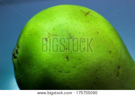 part of the green pear, pear on a blue background, the rear part of the pear