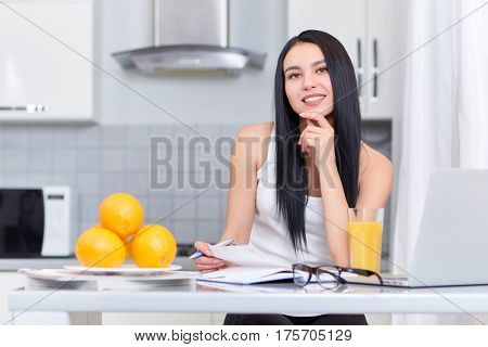 Portrait of smiling brunette girl with long hair studing on kitchen, holding pen in hand and looking at camera. Near on table laptop, books, glass of juice and plate with oranges.