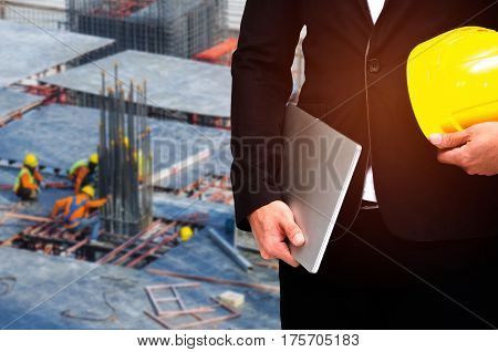 double exposure of businessman hold in hand yellow safety helmet and laptop industrial concept on construction site workers background, color tone effect.