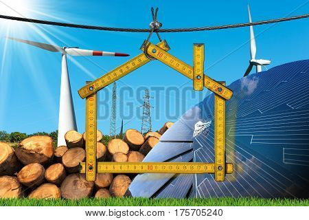 Wooden ruler in the shape of a house with renewable energies Wind (wind turbines) solar (solar panel) biomass (a stack of tree trunks) and a power lines