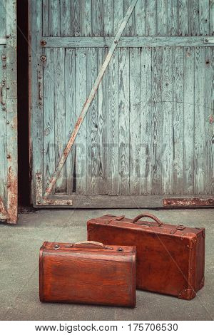 Two old leather suitcases stand against the background of the ajared garage gates