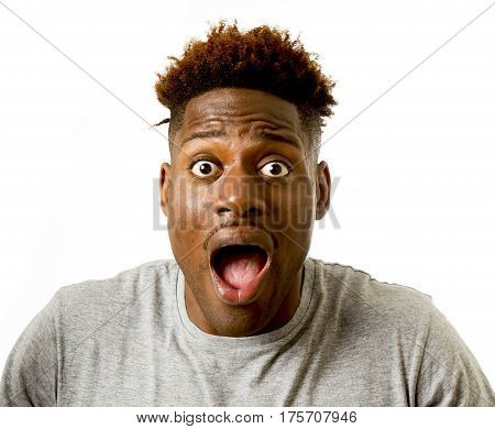 close up portrait of young attractive afro american man surprised with opened mouth and wide open eyes in disbelief amazed wow face expression isolated on white background
