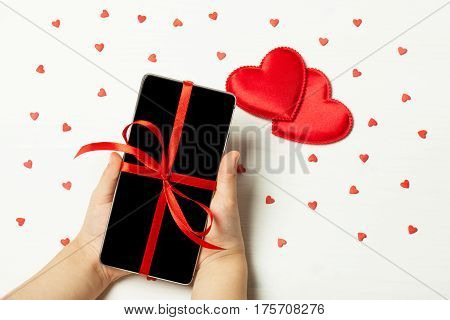 Children's hands hold the phone with festive ribbon. Against the background of hearts. The concept of St. Valentine's day Mother's Day birthday New Year Christmas Flat fly
