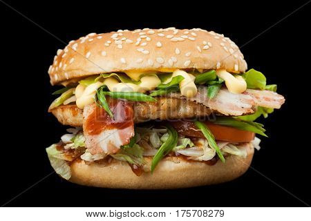 A delicious burger with bacon isolated on a dark background. Photo causing appetite. The concept of fast food delicious but unwholesome food. Photos can be used to create a menu or advertisement