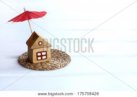 Small wooden house under a sun umbrella / a place for secluded rest