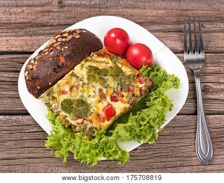 Vegetable baked pudding with bread and tomatoes on the wooden surface