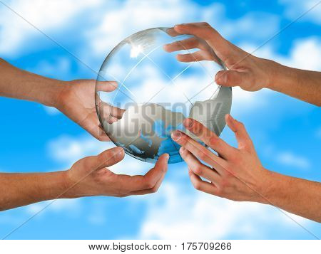 Hands supporting a transparent globe. The background of blue sky