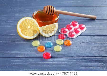 Cough drops with honey and lemon on wooden background