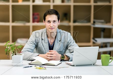 Portrait of young Businessman or corporate Trainee at cozy working Place with Computer Stationery Flower and green Mug