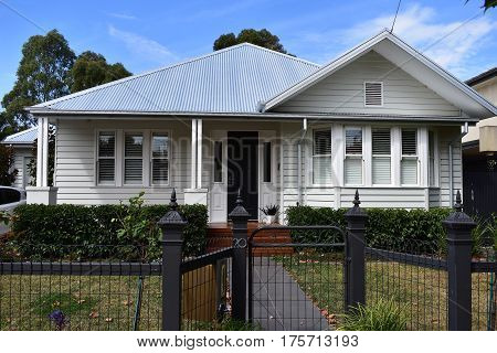 house white weatherboard with grey roof with black iron fence on sunny day family home