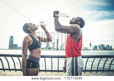 Couple running in New York - Sportive man and woman training outdoors and resting after a run