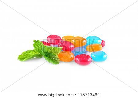 Different cough drops with sprig of mint on white background