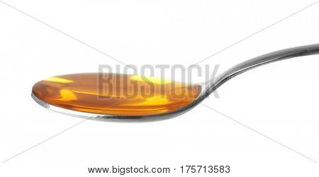 Yellow cough medicine syrup in silver spoon isolated on white