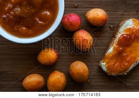 Apricot jam apricotes and toast with jam on the old board.Still life photography.