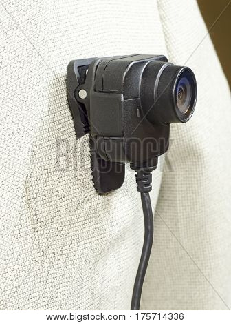 lens from the camcorder security police body camera in a white suit jacket shown from the side