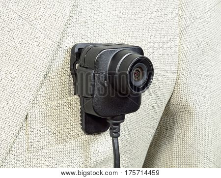 lens from the camcorder security police body camera with power cord in black color on a white suit jacket
