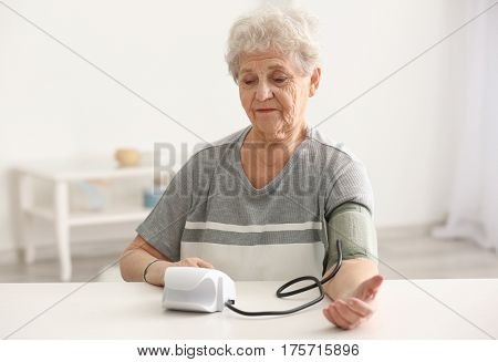 Elderly woman measuring pressure with digital sphygmomanometer while sitting at table