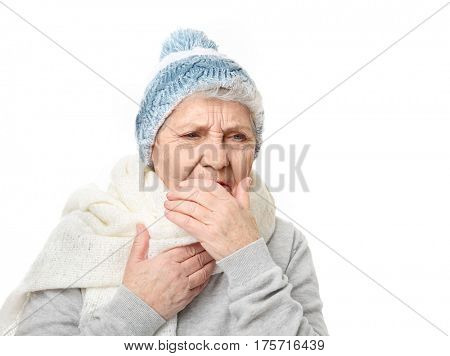 Portrait of coughing elderly woman in warm outfit on white background