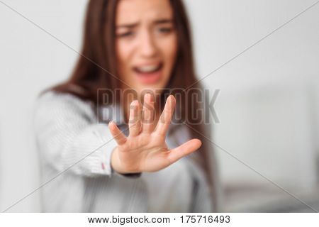 Depressed young woman with outstretched arm at home