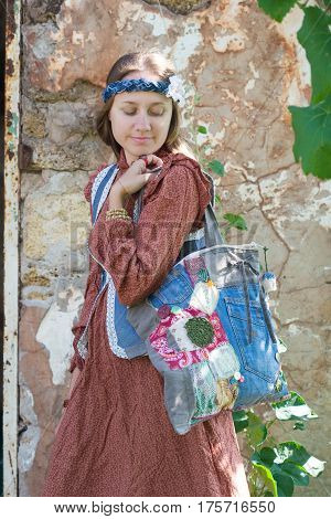 girl hippie clothes style folk at the stone wall
