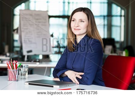Beautiful Business Lady in official clothing black Jacket and white Shirt sitting at grey Table with Computer Flower other Business and Lifestyle Items smiling Face satisfied with good Job well done.