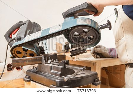 Mans hand cuts rolled metal products on bandsaw. Metallic product equipped in vice of cutting machine. Worker holding in one hand machine handle and other lying on table