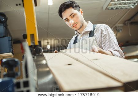 Young worker holding and looking at two plankings at angle. Inspection carried out on frame woodworking machine. Man dressed in plaid shirt with rolled up sleeves and working overalls