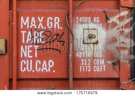 Red container weights and dimensions indications with graffitis