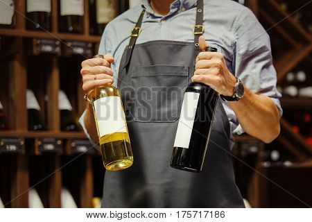 Young sommelier holding bottle of red wine in cellar. Expert in winemaking on background of shelves with wine