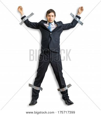 Businessman in suit is taped to the wall with adhesive tape. Isolated on white background.
