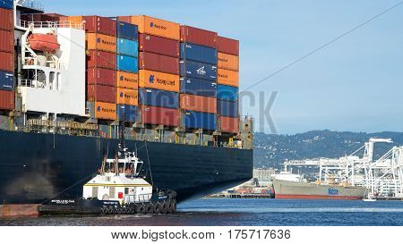 Oakland CA - March 07 2017: Tugboat MICHELLE SLOAN off the port quarter of NYK ATHENA assisting the vessel to maneuver out of the Port of Oakland.